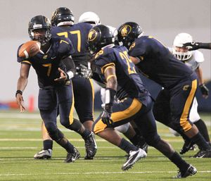Nimitz quarterback Darrell Stewart (7) tosses the ball to running back Joseph Love (25) during the first half of a high school football game at W.W.Thorne Stadium Thursday.