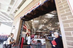 Customers and employees of Costco walk by a roll up door that was hit by a van during an attempted break-in on Tuesday morning. MCSO detectives are searching for those responsible for the more than $5,000 in damage to the building.
