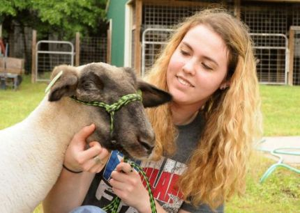 Lauren Thomason, The Woodlands High School FFA member, talks to her lamb, Archie, at The Woodlands FFA Barn. Photograph by David Hopper