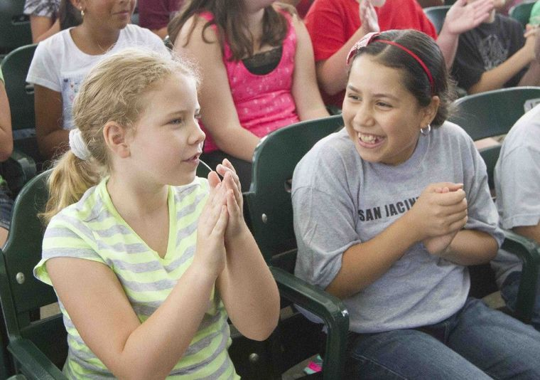 San Jacinto Elementary fourth graders Autumn Hole and Amaris Hernandez cheer during the Fine Arts Education Day at Cynthia Mitchell Woods Pavilion Wednesday.