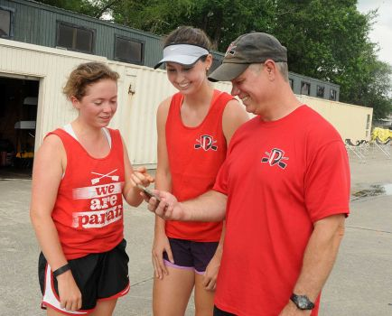 Audrey Brown and Amy Smith check their times with head coach Mike Rosman during the Parati competitive rowing practice at Nortshore Park in The Woodlands.