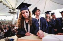 Graduates sign a book as part of a College Park tradition during their graduation on Monday at the Cynthia Woods Mitchell Pavilion