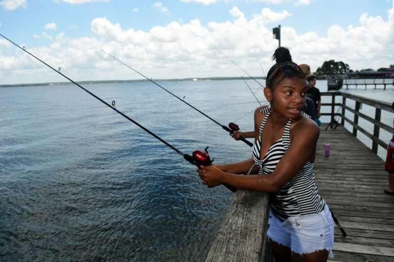 Makayla Perryman, 16, an 11th grader at Oak Ridge High School, tries her luck at fishing during the Conroe ISD Police Activity League summer camp program picnic at Lake Conroe Park on Friday, July 17, 2015.