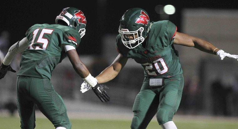 The Woodlands defensive back AJ Mason celebrates with defensive back Antoine Winfield Jr. after intercepting a pass from Cy-Fair quarterback Taylor Gray during a high school football game Friday.