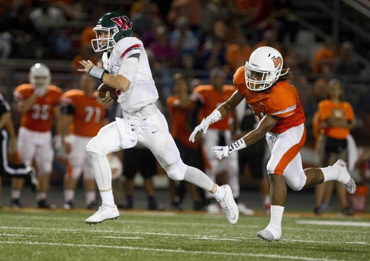 The Woodlands quarterback Eric Schmid runs for a 55-yard touchdown in the third quarter of a high school football game Friday.