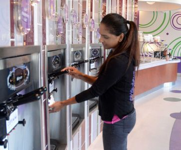 Franchise owner Shalini Nair puts flavored yogurt in a cup at Cups Frozen Yogurt, 1950 Hughes Landing Boulevard #1700 in The Woodlands. Nair has opened the first Houston area franchise of New Jersey based Cups Frozen Yogurt.