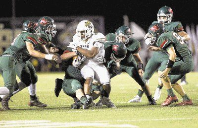 Conroe wide receiver Kameron Williams is surronded by The Woodlands' defense during a football game Friday