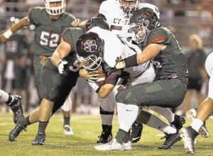 The Woodlands teammates Matt Mahoney, left, and Christian Cargol bring down Cy-Fair quarterback Taylor Gray. The Highlanders play host to Summer Creek in a District 16-6A game on Thursday night at Woodforest Bank Stadium.