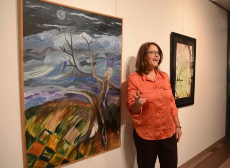 """College Park High School art instructor Tammi Madera explains her thoughts behind her painting of """"Grounded by My Roots, Swayed by Desires"""" to guests during the exhibit opening night at Lone Star College-Montgomery's Mary Matteson-Parrish Art Gallery. LSC-M art department is hosting the exhibit showcasing the talent of area local high school art teachers"""