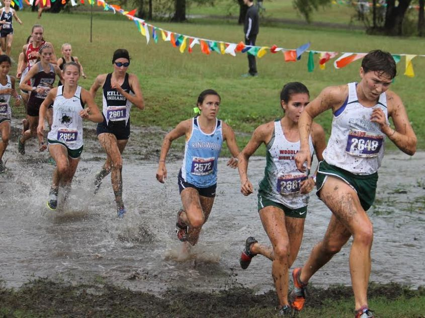 Kingwood Mustang Abby Guidry crosses a drainage gully at the UIL State Cross Country Championship on Saturday.  Kingwood finished fourth in the 6A team competition.