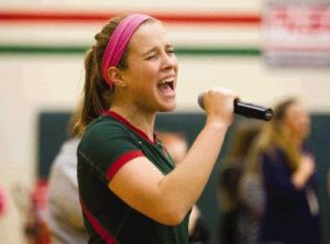 The Woodlands Hannah Hickman sings the National Anthem before the varsity volleyball team's game against Kingwood Tuesday.