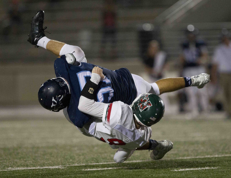 Kingwood's Benn Beckelman drives The Woodlands quarterback Harry Woodberry into the ground in the fourth quarter of a District 16-6A football game November 5, 2015, in Humble.