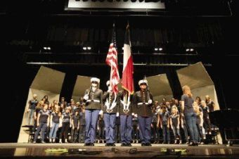 The Woodlands College Park High School JROTC color guard members present the U.S. and Texas flags as choir students perform the National Anthem during the Songs of Freedom choir tribute to veterans on Saturday at The Woodlands College Park High School