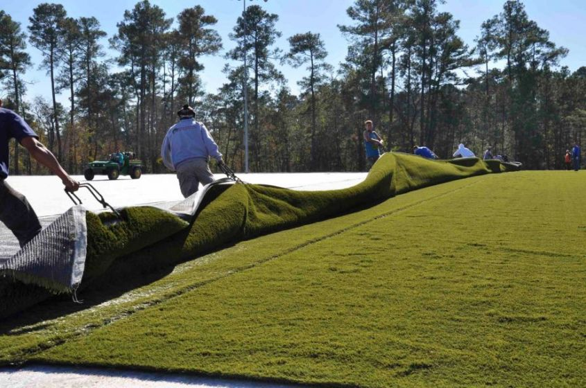 Workers put down turf in Bear Branch Park in The Woodlands. Some critics nationwide are voicing health concerns about the material's crumb rubber filler.