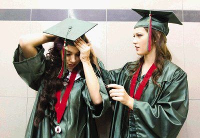 The Woodlands' Emily Fortey, left, gets some help with her cap from Christine Sulyukmanov before the mid-year commencement ceremony at Conroe High School Thursday.