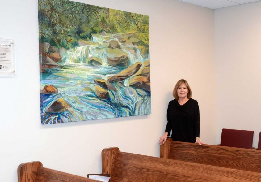 Judge Mary Ann Turner stands by a painting painted by juveniles at the MoCo Juvenile Justice Center in her County Court at Law #4 courtroom, 210 W. Davis Street in downtown Conroe.