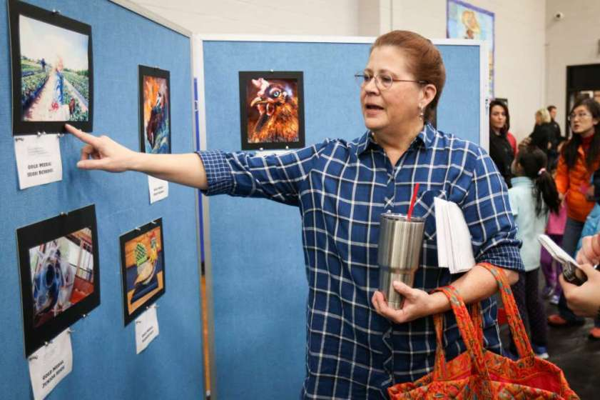 College Park teacher Leslie Lewis, who had four students in the Conroe ISD Western Art Show, chats about the various award winners on Saturday, Jan. 7, 2017, at Oak Ridge 9th Grade Campus.